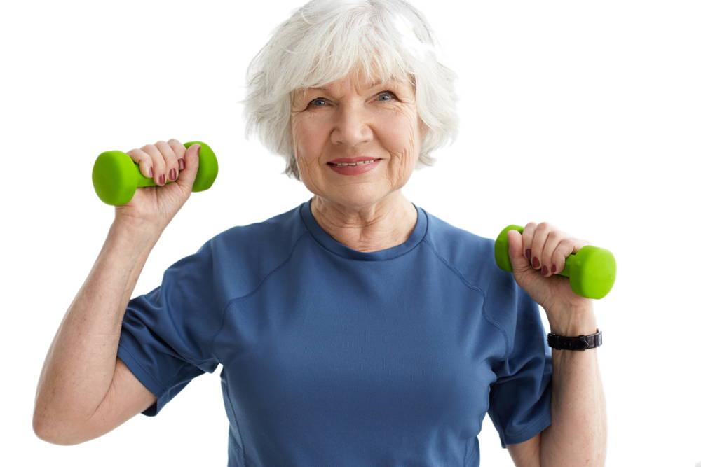 Seniorka ćwiczy hantlami rozciągając kręgosłup