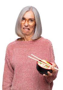 Starsza kobieta z obrzydzieniem patrzy na jedzenie